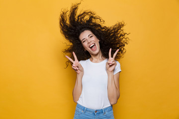 Image of european woman 20s laughing and having fun with shaking hair, isolated over yellow background Wall mural