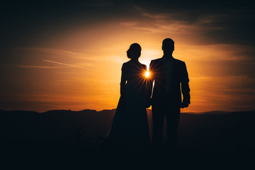 Man and woman silhouette, wedding couple. Orange sun ray between them