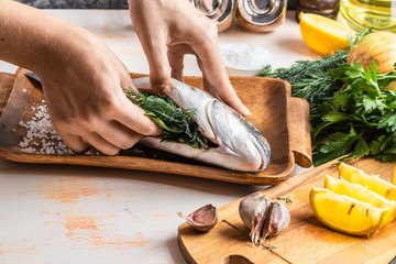 Process of cooking Dorado fish with lemon, olive oil and herbs. Female hands close-up. Concept of homemade food, culinary hobby Wall mural