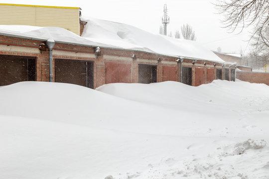 Huge snow banks near garage doors in winter during blizzard
