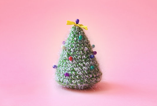 Knitted Christmas tree bound of green yarn with multicolored pins on it. Christmas holiday concept in minimalism style.