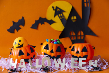 Happy Halloween with haunted house castle and pumpkins bucket and bat on orange background.Halloween theme