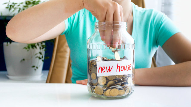 Closeup photo of young woman throwing money in glass jar with savings for buying new house