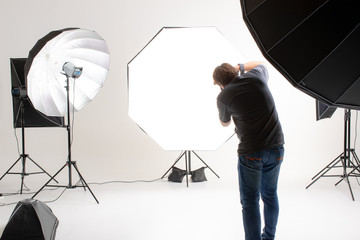 Photographer  working in modern lighting studio with many kinds of flash and accessories. taking to empty area in look like shot to someone. Idea for adding people or object to photo