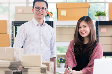 Young Asian couple business  working in simple house office look like doing startup business. Concept for online marketing, SME and home base workplace