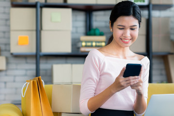 Young Asian beautiful girl is happy smiling to shopping online with smartphones and other order items she buys around her. Concept technology makes us live more comfortable and easy to tread