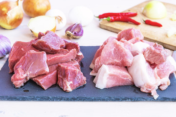Pieces of raw pork meat and beef and ingredients for minced meat