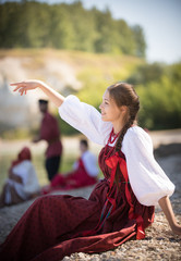A girl in Russian national costume pose for the camera on the background of an amazing landscape