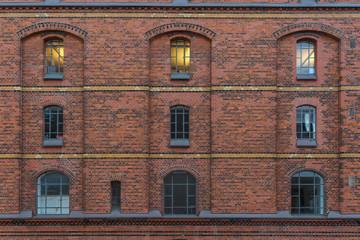 Fassade in der histori8schen Speicherstadt in Hamburg mit einem beleuchteten Fenster