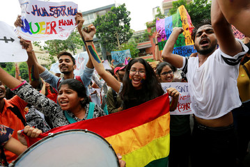 Supporters of the lesbian, gay, bisexual and transgender (LGBT) community hold placards as they celebrate the Supreme Court's verdict of decriminalizing gay sex and revocation of the archaic Section 377 law, during a march in New Delhi