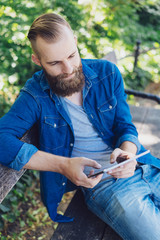 Man relaxing using a tablet on a park bench