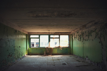 Empty room with broken windows in ruined abandoned building inside interior