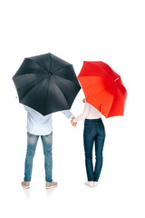 back view of young couple with black and red umbrellas holding hands isolated on white