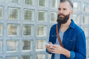 Serious bearded man standing holding a mobile