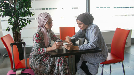 Two muslim girls talking and showing pictures on their phone