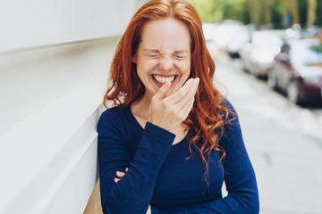lachende frau hält sich eine hand vor den mund