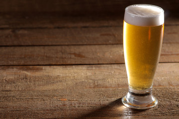 A glass of light beer on a wooden brown background with a place for an inscription