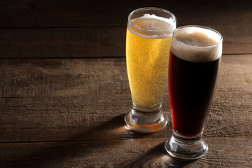 A glass of light and a glass of dark beer on a wooden brown background with a place for an inscription