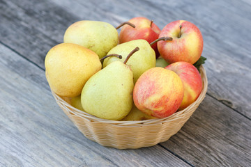 Fresh apples and pears in wicker plate on wooden background in rural style