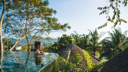 Girl in a beautiful infinite pool surrounded by tropical forest