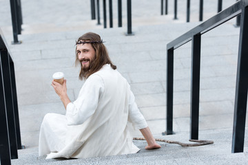 back view of smiling Jesus in robe and crown of thorns sitting on stairs and holding disposable coffee cup on street Wall mural