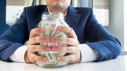 Closeup photo of young greedy businesman holding glass jar full of money in hands