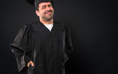 Man on his graduation day University unhappy and suffering from backache for having made an effort on black background
