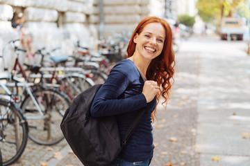lachende junge frau mit rucksack ist in der stadt unterwegs