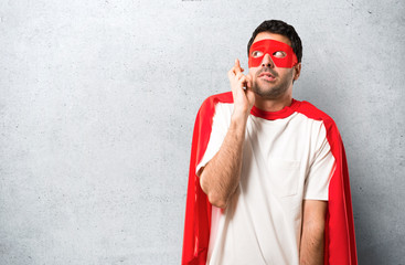 Superhero man with mask and red cape with fingers crossing and wishing the best. Making a wish. on textured grey background