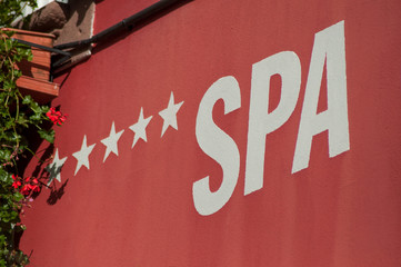 closeup of five stars hotel spa signage on red stoned wall