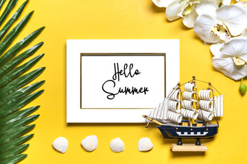Palm, monstera leaves, orchid, seashells, white photo frame, ship on yellow background. Concept Hello summer, let's go travel, holiday, summertime Flat lay Top view Copy space Mock up