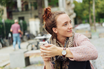 friendly woman sitting on a bench holding her smart phone
