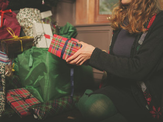 Young woman placing christmas present under tree