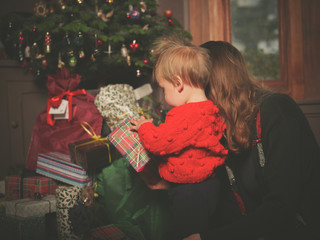 Mother and little child opening christmas presents