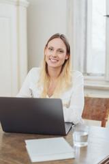 lächelnde blonde frau arbeitet am laptop