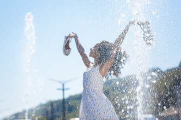 Feeling of freedom. Selective focus of fountain water drops with happy beautiful woman standing in the background Wall mural