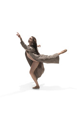 Beautiful slim young female modern jazz contemporary style ballet dancer in silhouette wearing beige long cloak isolated on a white studio background