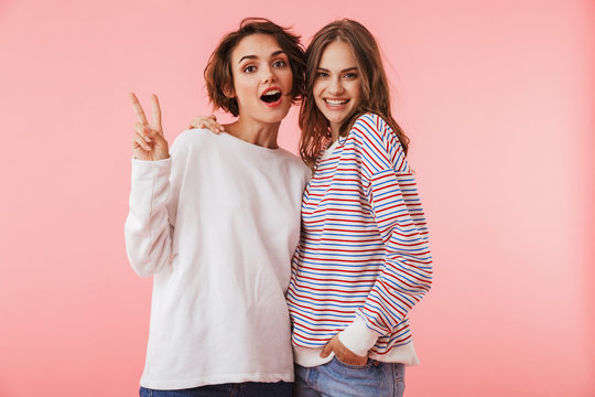 Women friends isolated over pink wall background posing.