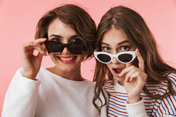 Emotional young women friends isolated over pink wall background wearing sunglasses.