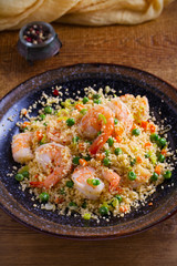 Shrimps with couscous, green peas, leeks and carrot. vertical