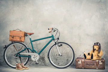 Photo sur Plexiglas Velo Retro bicycle with leather mailman's bag, old sneakers and Teddy Bear toy in leather aviator's hat and goggles sitting on aged classic travel suitcase front concrete wall. Vintage style filtered photo