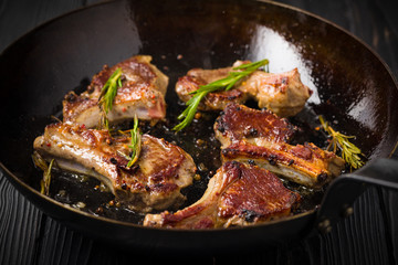 Lamb chops frying in a rustic metal pan with rosemary and mixed pepper