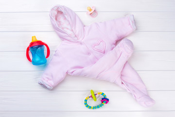 Pink baby girl fleece coverall and toys.