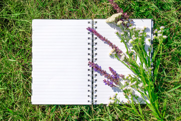 Open notepad with white paper on background of green grass and poppy meadow flowers. Natural, ecological mockup. Blank notebook recycle paper open two page with copy space area on lawn with sunlight