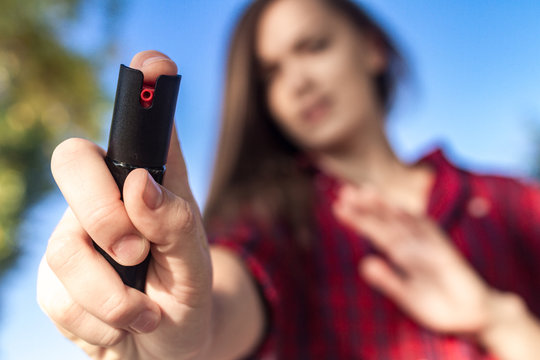 Self-defense. A young woman protects herself in the park from criminals, thieves and hooligans with the help of pepper spray. Self defense woman