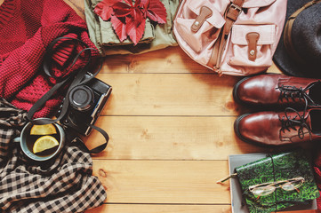 Wall Mural - autumn women fashion clothes set with cozy sweater, shoes, plaid shirt, vintage photo camera, backpack and cup of tea. Fall seasonal walk concept, flat lay with empty space