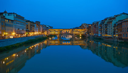 "Famous bridge ""Ponte Vecchio"" in Florence in Italy at night / Illuminated bridge with nice reflections in the water"