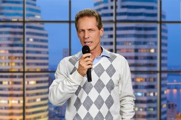 Man with microphone on skyscraper background. Confident middle-aged man talking into microphone on evening city background.