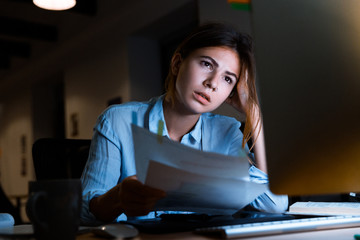 Woman graphic designer using pc computer working with documents at night in office.