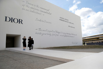 Guests take pictures in front of the venue for fashion house Dior Spring/Summer 2019 women's ready-to-wear collection show during Paris Fashion Week